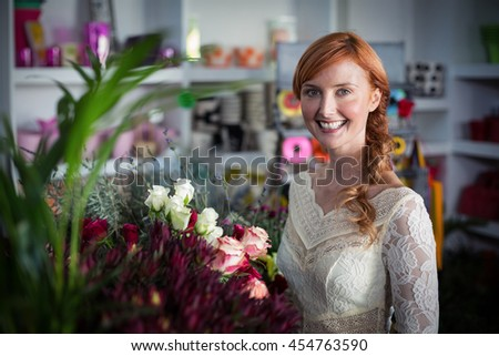 Female florist standing and smiling in the shop - stock photo