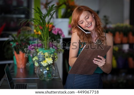 Female florist taking order on mobile phone in flower shop - stock photo