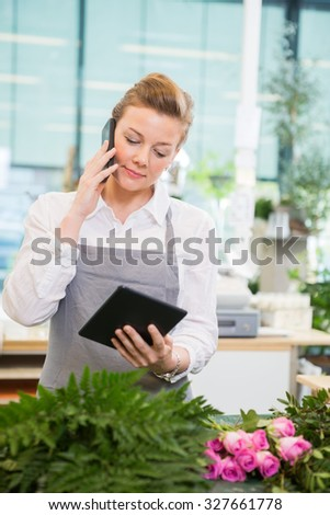Female florist using mobile phone and digital tablet at counter in flower shop - stock photo