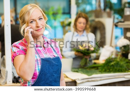 Female Florist Using Mobile Phone In Flower Shop - stock photo
