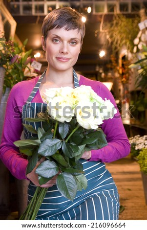 Female florist with bunch of roses, smiling, portrait - stock photo