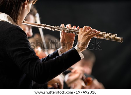 Female flutist performing, hands close-up on dark background. - stock photo