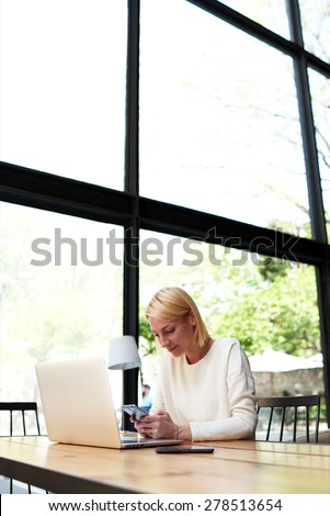 Female freelancer connecting to wireless on her smart phone at coffee shop, modern business woman typing text message oh cell phone while working in loft studio with laptop computer, flare sun light - stock photo