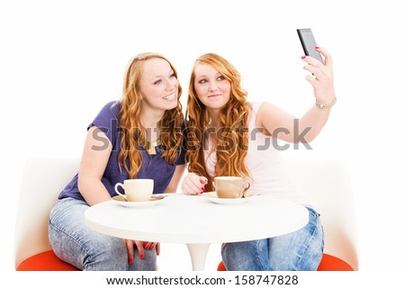 female friends at a coffee table making photos from themselves on white background - stock photo