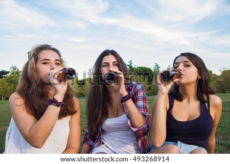 Female friends celebrating the holiday having a good time drinking beer in a park. They're happy. The three girls are drinking at a time.