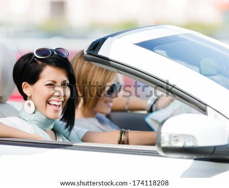 Female friends driving car and having fun on the vacation - stock photo