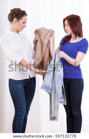 Female friends during exchanging their jackets, vertical - stock photo