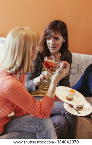 Female Friends Eating Delicious Dessert And Socializing At Home