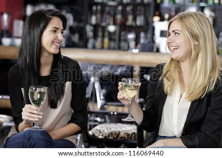 female friends enjoying a drink together at a wine bar. - stock photo