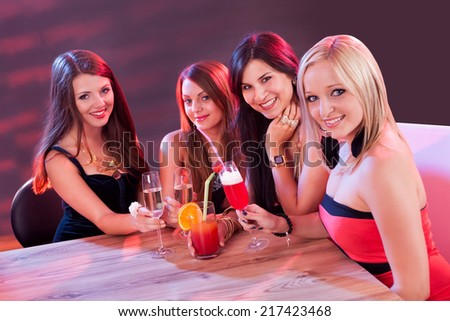 Female friends enjoying a night out sitting having cocktails at a table in a nightclub - stock photo