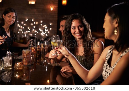 Female Friends Enjoying Night Out At Cocktail Bar - stock photo