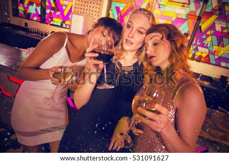 Female friends having glass of champagne and wine against flying colours