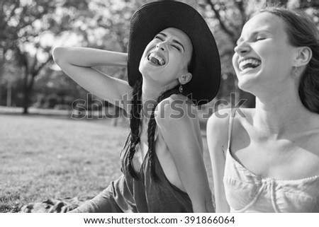 Female friends in the park sitting on the grass in joyful in sunny day - stock photo