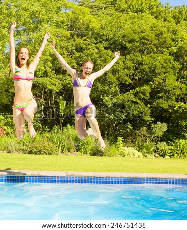 female friends jumping in pool - stock photo
