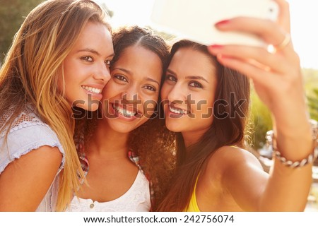 Female Friends On Holiday Taking Selfie With Mobile Phone - stock photo