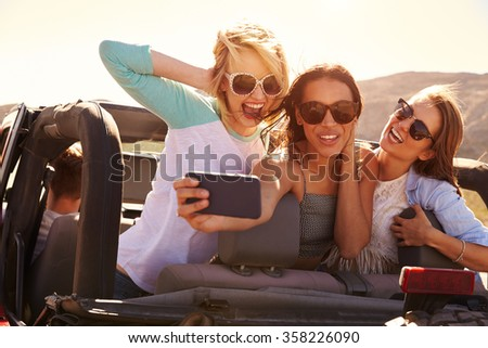 Female Friends On Road Trip In Convertible Car Taking Selfie - stock photo