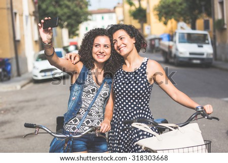 Female friends taking a selfie with their bicycles in the city. They are two women, a couple or sisters, wearing summer clothes and looking at their smart phone. There are some houses on background. - stock photo