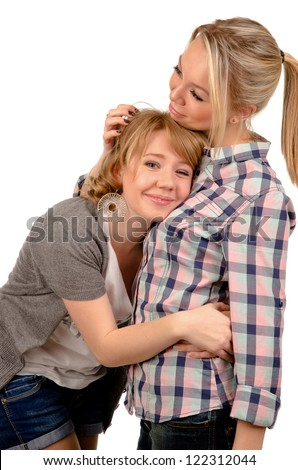 Female friends taking comfort from each other hugging each other and smiling isolated on white - stock photo