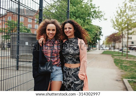 Female friends together walking along city street. Happy young women having fun outdoors.