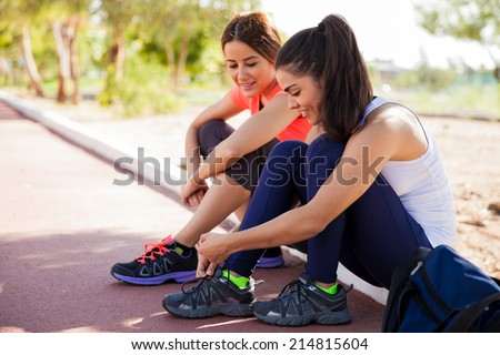 Female friends tying their shoes and getting ready to go for a run at a track - stock photo