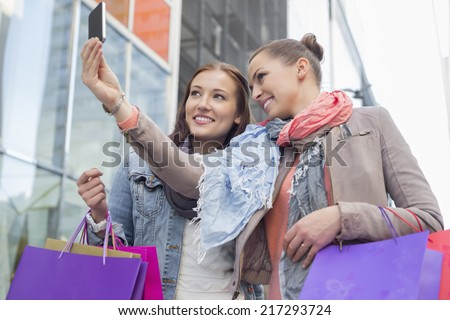 Female friends with shopping bags taking self portrait through mobile phone - stock photo