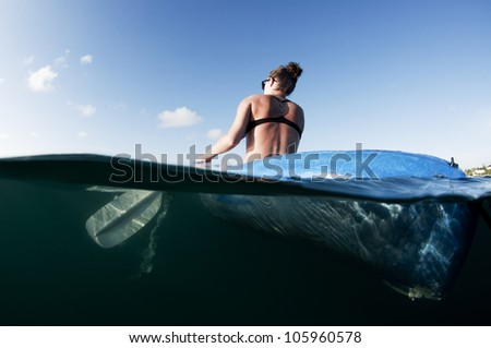 female from behind paddling a kayak on the ocean - stock photo