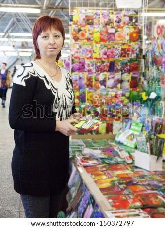 Female gardener buys the seeds on the market