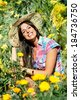 Female gardener surrounded by yellow flowers and plants. Successful woman enjoying her hobby. - stock photo