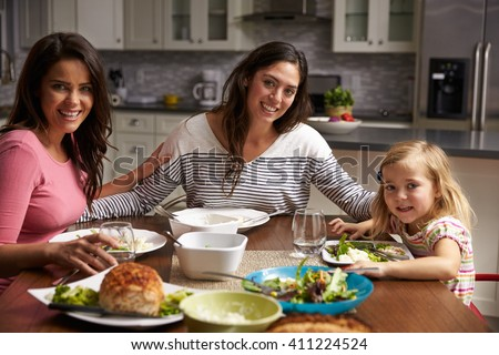 Female gay couple and daughter dining at home look to camera - stock photo