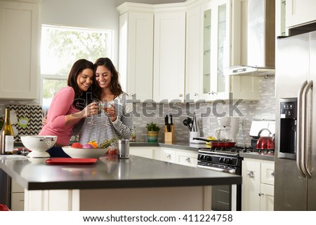 Female gay couple embracing make a toast in the kitchen - stock photo