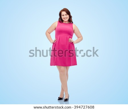 female, gender, portrait and people concept - smiling happy young plus size woman posing in pink dress over blue background - stock photo