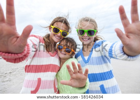 Female girl children having fun wearing sunglasses & waving to a camera taking selfie photograph on a beach - stock photo