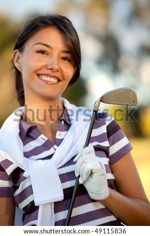 Female golf player outdoors holding a club and smiling - stock photo