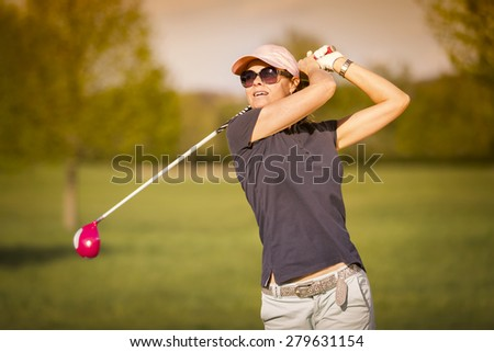 Female golf player swinging driver club from tee box at twilight. - stock photo