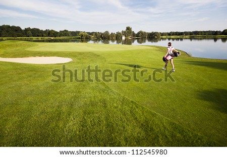 Female golf player walking  towards green on fairway carrying golf bag with clubs, lake in background. - stock photo