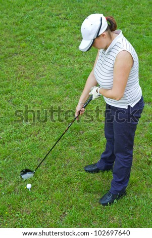 female golf player with a golf club - stock photo
