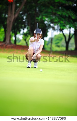 Female golf player with putter squatting to analyze the green at golf course - stock photo