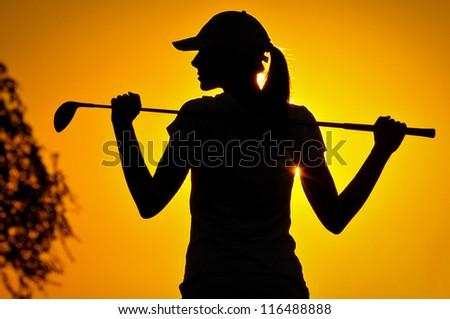Female golfer at sunrise - stock photo