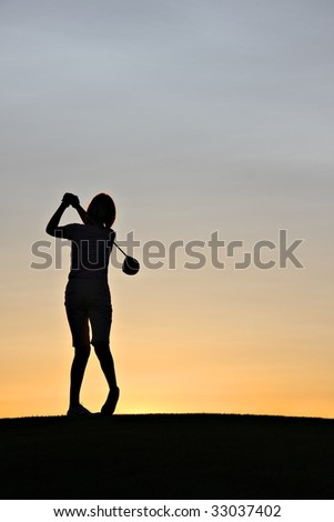 Female golfer swinging a driver at sunrise. - stock photo