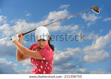 Female golfer swinging golf driver during sunny day - stock photo