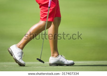 Female golfers walking on green with putter. - stock photo