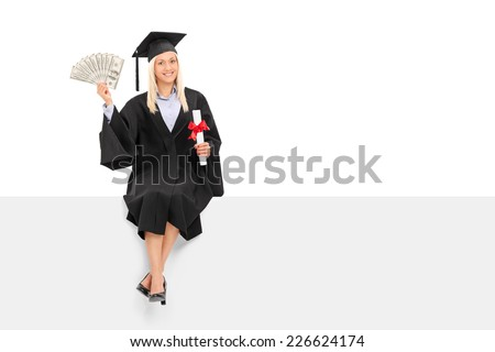 Female graduate holding money seated on a panel isolated on white background - stock photo