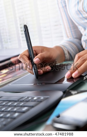 Female graphic designer working in office using tablet pen, selective focus