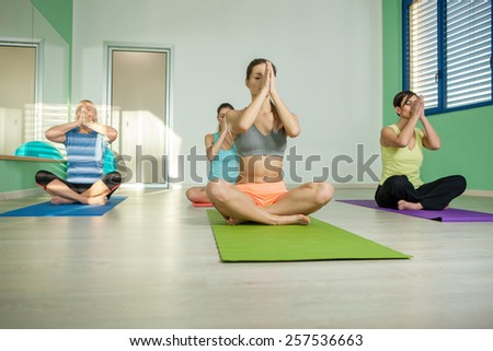 Female group is doing yoga exercises in a fitness club