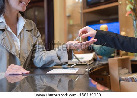female guest being handed over the keys to hotel room by receptionist, travel and tourism concept - stock photo
