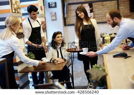 Female guest sitting at table in cafeteria, served by four waiters. - stock photo