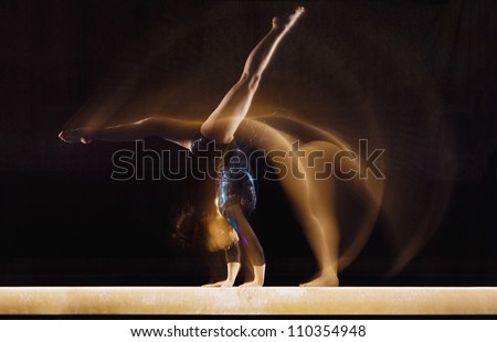 Female gymnast in motion on balance beam - stock photo