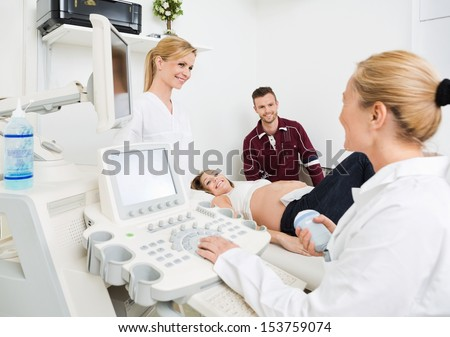 Female gynecologists and expectant couple undergoing ultrasound scan in clinic - stock photo