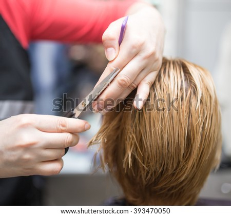 Female hair cutting scissors in beauty salon