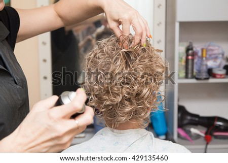 Female hair lacquer in a beauty salon